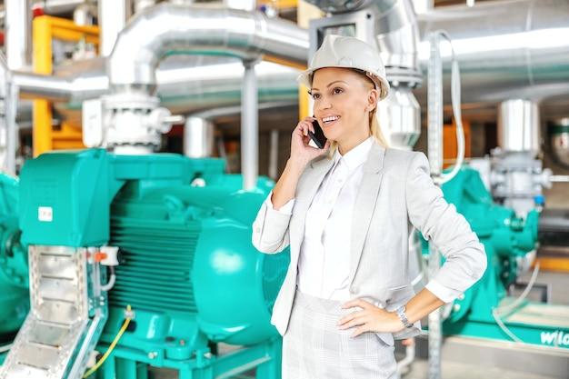 Sorridente imprenditrice amichevole con il casco sulla testa in piedi nella centrale elettrica con la mano sul fianco e parlare con il partner commerciale al telefono.