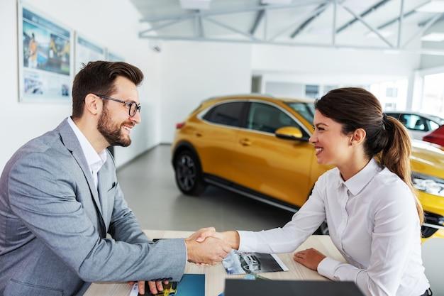 Venditore di auto sorridente e amichevole seduto al tavolo con un cliente e stringe la mano. la donna ha appena comprato una macchina nuova ed è molto soddisfatta.