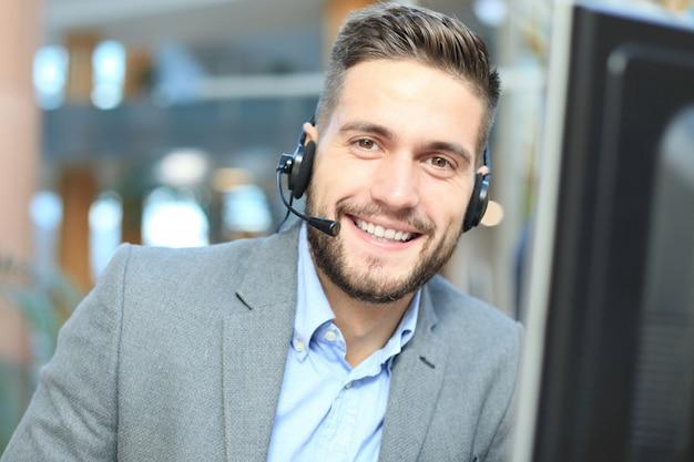 Operatore di call center maschio giovane bello sorridente amichevole.