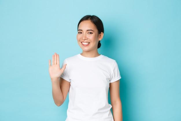 Sorridente ragazza asiatica dall'aspetto amichevole in maglietta bianca agitando la mano in un gesto di saluto, dicendo ciao, salutando la persona e in piedi sfondo blu felice, felice di incontrare qualcuno