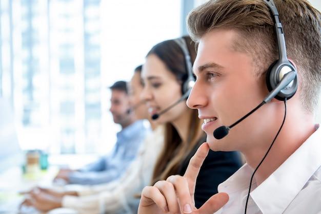 Uomo amichevole sorridente che lavora nell'ufficio di call center con la squadra