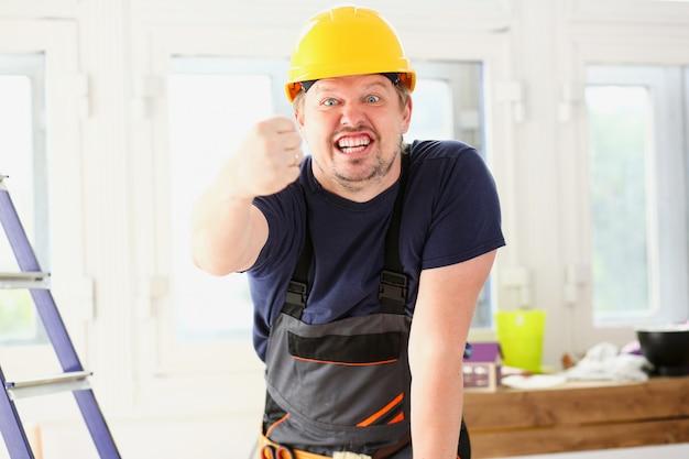 Lavoratore divertente sorridente nella posa gialla del casco