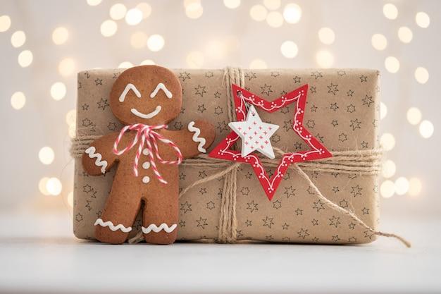Uomo di pan di zenzero sorridente con regalo e luci