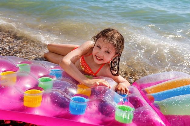 La ragazza sorridente sulla spiaggia in estate su un materasso ad aria sulla spiaggia esamina la macchina fotografica. concetto di intrattenimento estivo