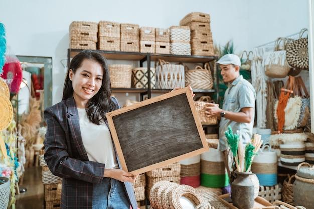 La ragazza sorridente in un blazer che tiene una lavagna sta in un negozio di artigianato con un cliente che sta selezionando l'artigianato