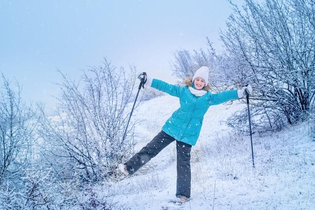Ragazza sorridente in abiti invernali blu con bastoni da passeggio scandinavi sta camminando nel parco.