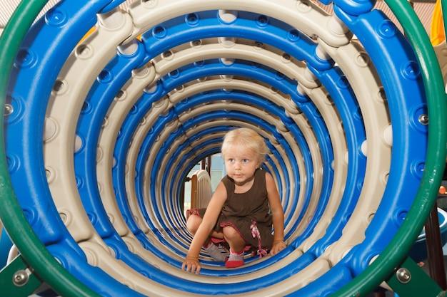 Ragazza sorridente che si arrampica attraverso il tubo del parco giochi