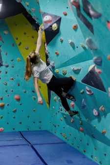 La ragazza sorridente si arrampica sulla parete da arrampicata, la donna è impegnata in sport estremi, arrampicata su roccia in città, allenamento di forza e resistenza