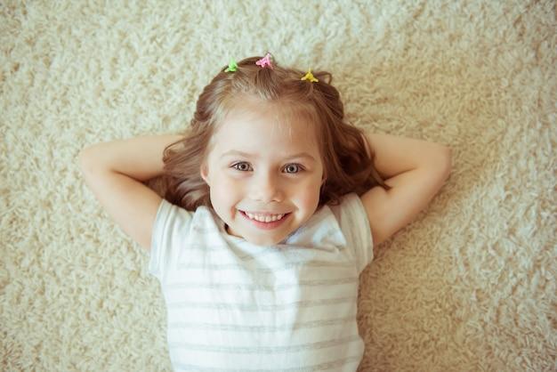 La ragazza sorridente in un vestito si trova sul tappeto bianco