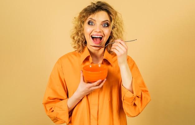 La ragazza sorridente fa colazione. donna attraente con ciotola e cucchiaio. mangiare cibo sano. dieta, calorie, assistenza sanitaria.