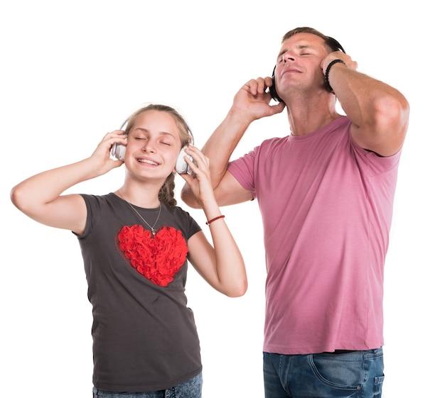 Ragazza sorridente e padre in cuffia che ascolta la musica su una parete bianca