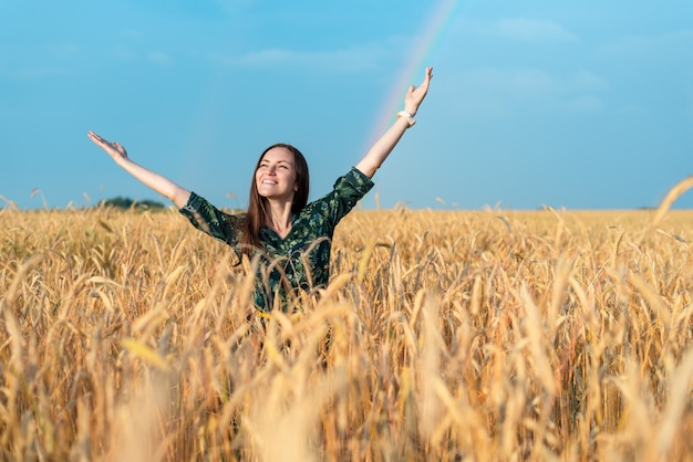 Ragazza sorridente in un campo con grano che esamina le mani del cielo che tirano su, concetto di libertà