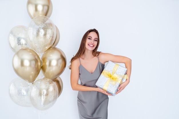 La ragazza sorridente tiene in mano una grande scatola regalo avvolta mentre si trova vicino ai palloni d'aria è venuta alla celebrazione della festa