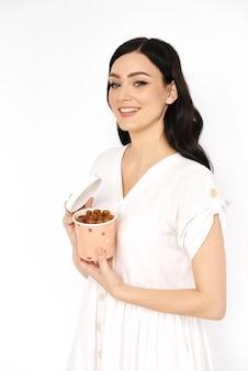 La ragazza sorridente tiene la scatola di carta con la pastiglia di frutta