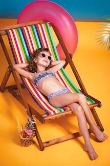 Ragazza sorridente in costume da bagno lilla e occhiali da sole sdraiati sulla sedia a sdraio arcobaleno con le gambe incrociate e prendere il sole