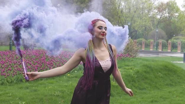 Ragazza sorridente in abito di raso viola con lunghe trecce multicolori e trucco scintillante accattivante. il fumo di colore viola copre la ragazza nel parco primaverile
