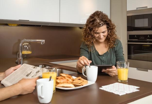 Ragazza sorridente che legge le notizie su un tablet a colazione