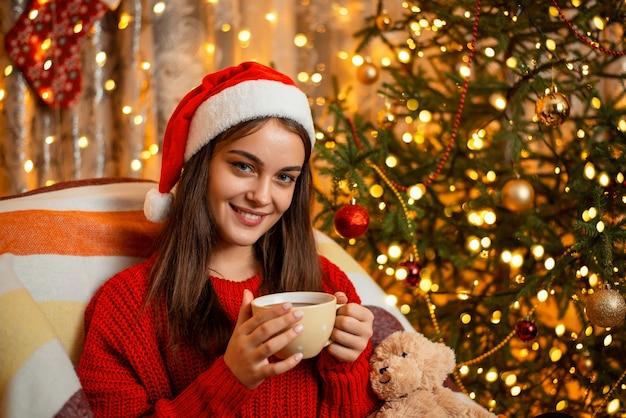 Ragazza sorridente in cappello rosso della santa con una tazza di cioccolata calda