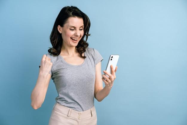 La ragazza sorridente si rallegra della sua vittoria, guardando il telefono.