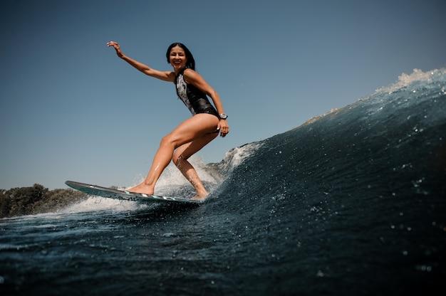 Ragazza sorridente che guida sul wakeboard sul lago