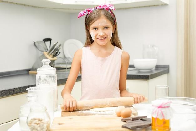 Ragazza sorridente che arrotola la pasta su una cucina disordinata