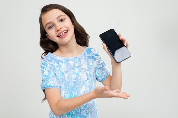 La ragazza sorridente mostra uno schermo del telefono in bianco con un modello su uno studio