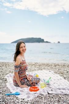 La ragazza sorridente si siede su un copriletto su una spiaggia di ciottoli con giocattoli per bambini