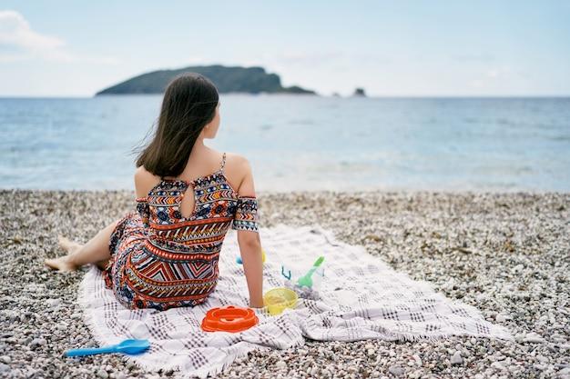 La ragazza sorridente si siede su una coperta su una spiaggia di ciottoli e guarda il mare