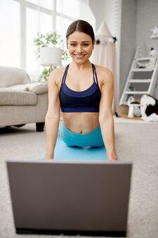 La ragazza sorridente si siede sul pavimento a casa, formazione in linea in forma al computer portatile. persona di sesso femminile in abbigliamento sportivo, allenamento sportivo internet, interno della stanza