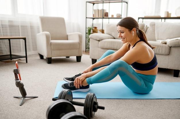 La ragazza sorridente si siede sul pavimento a casa, allenamento fitness in linea al computer portatile. persona di sesso femminile in abbigliamento sportivo, allenamento sportivo internet, interno della stanza