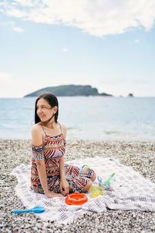 Sorridente ragazza seduta su una coperta su una spiaggia di ciottoli girando di lato
