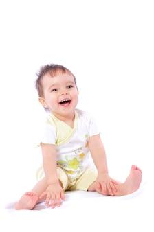 Ragazza sorridente che si siede sul pavimento