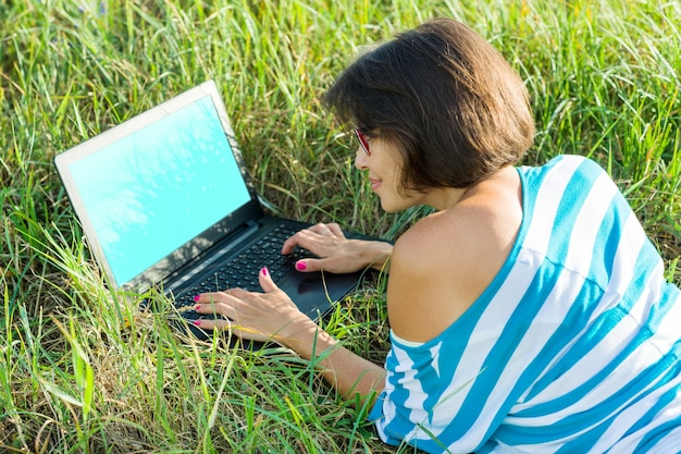 Ragazza sorridente che si siede sull'erba in una luminosa giornata estiva e lavora al computer