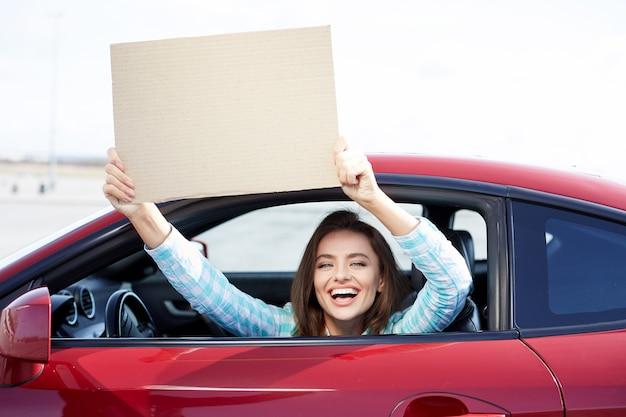 Ragazza sorridente che si siede all'interno della macchina rossa, autista felice. donna che guarda la fotocamera e sorridente, tenendo il foglio di carta, mock up. testa e spalle del felice proprietario di un'auto nuova