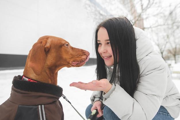 La ragazza sorridente per strada alimenta un bellissimo zibellino marrone dalla sua mano, il cane sorride.