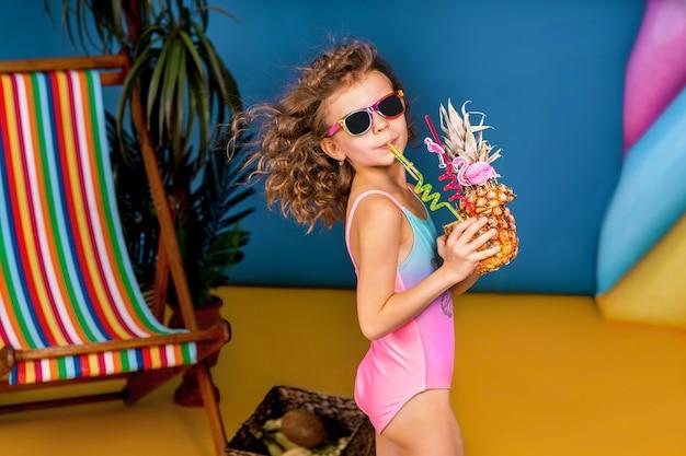 La ragazza sorridente in costume da bagno e occhiali da sole resta vicino al ponte arcobaleno c