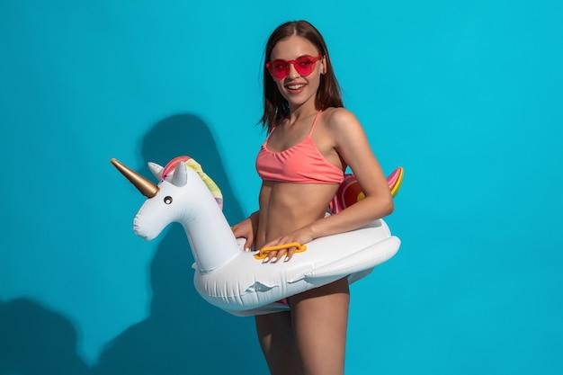 Ragazza sorridente in costume da bagno con anello di gomma unicorno sulla parete blu