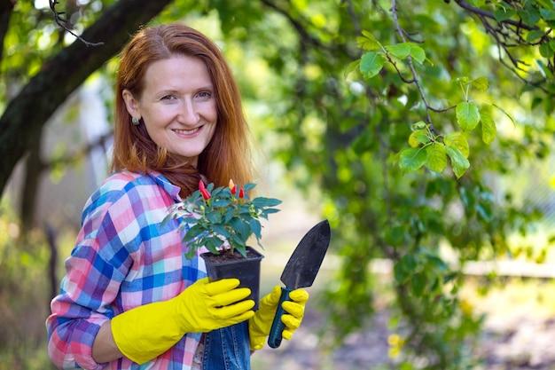 La ragazza sorridente trapianta i fiori nel giardino. vasi da fiori e piante da trapianto