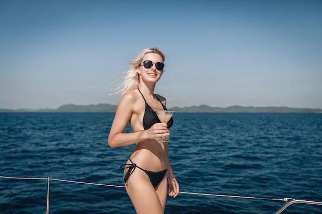Ragazza sorridente, che indossa un bikini nero e occhiali da sole, posa per la fotocamera, con in mano una bevanda fredda in un bicchiere.