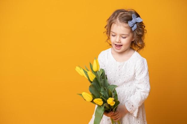 Ragazza sorridente in abito bianco su sfondo giallo. allegro bambino felice con bouquet di fiori di tulipani.