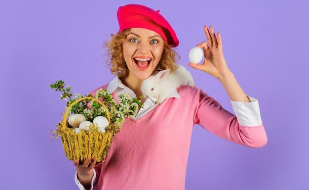 Ragazza sorridente con cesto di uova, piccolo coniglietto sulle spalle e uovo bianco in mano. buona pasqua. tradizione di pasqua.