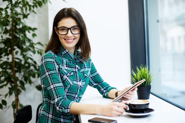Ragazza sorridente con i capelli neri che indossa camicia e occhiali da vista seduti in un caffè con tablet e tazza di caffè, concetto di freelance, ritratto, che guarda l'obbiettivo