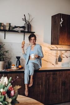 Ragazza sorridente con caffè e croissant. mattina di natale