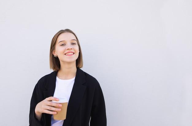 Ragazza sorridente con una tazza di caffè in sue mani, esaminando la macchina fotografica e sorridendo al bianco.