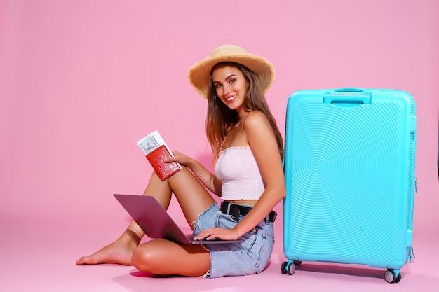 La ragazza sorridente con i soldi e il passaporto dei biglietti del computer portatile viaggerà seduta vicino alla valigia in sho...
