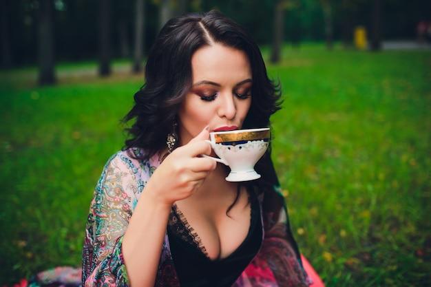 Ragazza sorridente con la tazza in mano. ragazza che beve il tè.