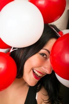 Ragazza sorridente con palloncini di palline rosse e bianche