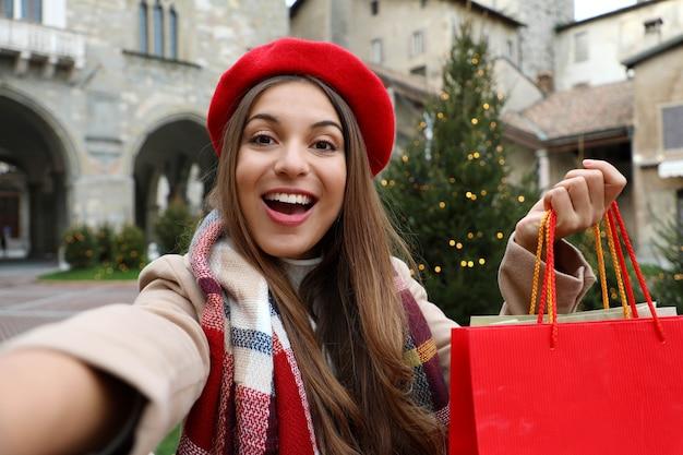 Ragazza sorridente con le borse della spesa in mano fa selfie a natale