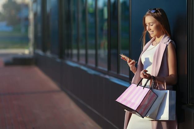 Ragazza sorridente con borse della spesa e guardando nel telefono