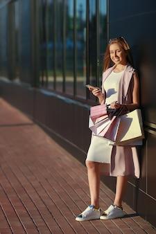 Ragazza sorridente con le borse della spesa con il telefono in mano.